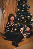 Pretty young woman near christmas tree in her cozy room Royalty Free Stock Photography