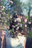 Pretty young woman near tree with flowers Stock Photo