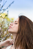 Pretty young woman near tree with flowers Stock Image