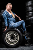 Pretty young woman near the wheels. Over black background Royalty Free Stock Photos