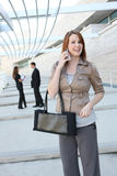 Pretty Young Woman at Office Building. A pretty young business woman at the office building on phone stock photo