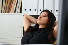 Pretty young woman in office sit at table finish all the work have a break can afford to relax royalty free stock photography