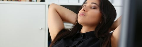 Pretty young woman in office sit at table finish all the work have a break can afford to relax stock photo