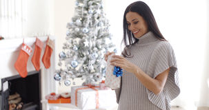 Pretty young woman opening a Christmas gift Royalty Free Stock Image