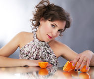 Pretty young woman with oranges reflects in mirror Royalty Free Stock Image