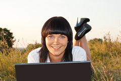 Pretty young woman outdoor with computer Royalty Free Stock Photography