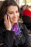 Pretty Young Woman Outdoor Lifestyle. Pretty young woman at an outdoor restaurant cafe speaking on a mobile phone Stock Photography
