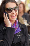 Pretty Young Woman Outdoor Lifestyle. Pretty young woman at an outdoor restaurant cafe speaking and laughing on a mobile phone Royalty Free Stock Photo