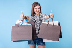 Pretty young woman with packages is gesturing Royalty Free Stock Images