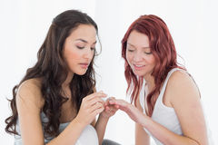 Pretty young woman painting a friends nails Stock Image