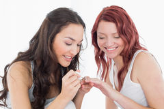 Pretty young woman painting a smiling friends nails Stock Images
