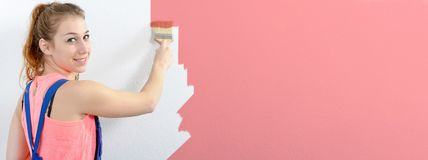 Pretty young woman painting the wall pink color, horizontal photo banner royalty free stock photography