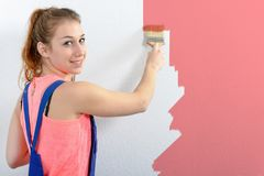 Pretty young woman painting the wall pink color. A pretty young woman painting the wall pink color Stock Photography