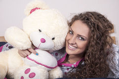 Pretty young woman in pajamas with teddy bear Stock Photography