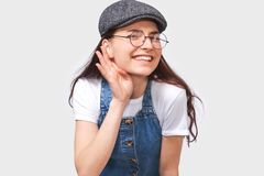 Pretty young woman paying attention and placing hand on ear asking someone to speak louder or whisper, posing on white wall. Smiling beautiful teenager girl stock image
