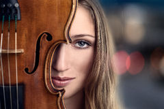 Pretty Young Woman Peeking Behind Violin Royalty Free Stock Photography