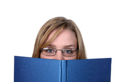 Pretty young woman peeking over top of book. Pretty young woman peeking over top of blue book Royalty Free Stock Images