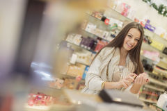 Pretty young woman in perfumery Stock Images