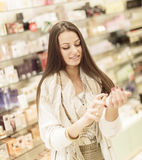 Pretty young woman in perfumery. Pretty young woman in the perfumery Stock Images