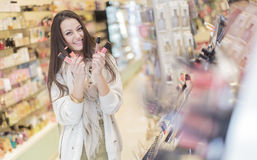 Pretty young woman in perfumery Royalty Free Stock Photos
