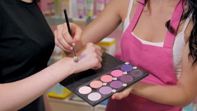 Pretty young woman in perfumery shop choose cosmetics with cosultant Royalty Free Stock Photos