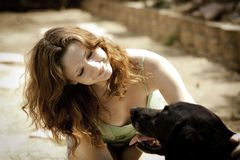 Pretty young woman petting her dog Stock Image