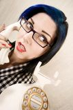 Pretty young woman on the phone. Apprehensive young woman talking on a vintage phone royalty free stock image