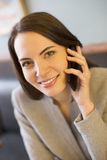 Pretty young woman on phone in coffee bar Royalty Free Stock Photography