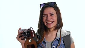 Pretty young woman photographer with old vintage camera taking picture, studio shot on white background. Beautiful stock footage