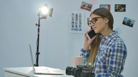 Pretty young woman photographer working with laptop and drinking coffee in the office.  stock video footage