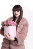 Pretty young woman in pink fur coat holding rose flowers in hat Stock Photos