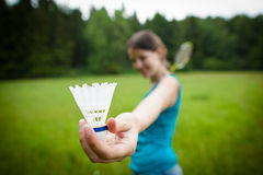 Pretty, young woman playing badminton. In a city park on a lovely summer day (shallow DOF Stock Images