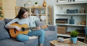 Pretty young woman playing the guitar in cozy apartment having fun alone. Pretty young woman is playing the guitar in cozy apartment having fun alone sitting on stock footage