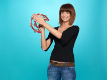 Pretty young woman playing a tambourine Royalty Free Stock Photos