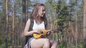 Pretty young woman playing the ukulele in a pine forest. Nature lover relaxing alone outdoors. Unity with wild nature stock video footage