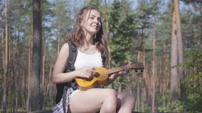 Portrait of pretty young woman playing the ukulele in a pine forest. Nature lover relaxing alone outdoors. Unity with stock footage