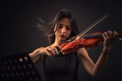 Pretty young woman playing a violin over black background royalty free stock photography