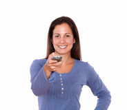 Pretty young woman pointing remote control Royalty Free Stock Photo