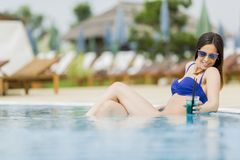 Pretty young woman in pool Stock Images