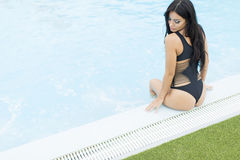 Pretty young woman by the pool Royalty Free Stock Image