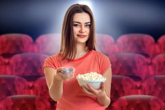 Pretty young woman with pop-corn watching movie stock photos