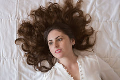 Pretty young woman portrait. Pretty young woman, with beautiful long hair lying on the bed Stock Images