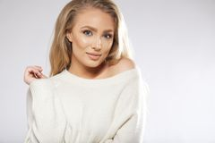 Pretty young woman posing against grey background. Portrait of pretty young woman posing against grey background. Young woman wearing sweater looking at camera Stock Image
