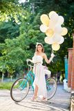Pretty young woman posing with colorful ballong near blue bike on park alley. Pretty young woman in long white dress posing with colorful balloons in her hand Stock Images