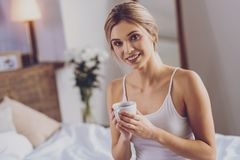 Pretty young woman posing with cup of coffee and smiling royalty free stock photos