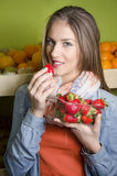 Pretty young woman posing while eating strawberries Royalty Free Stock Photos