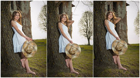 Pretty young woman posing in front of the farm. Very attractive blonde girl with white short dress holding a hat. Romantic girl Stock Photos
