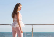 A pretty and young woman is posing near a noisy sea. Young lady with long light brown hair posing at a balcony in luxury hotel. stock image