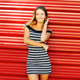 Pretty young woman posing near red wall Stock Photo