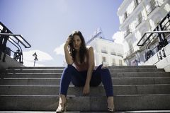 Pretty young woman posing on the stairs royalty free stock image